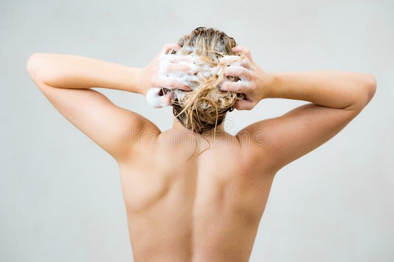 Frau, die Dusche nimmt und ihr Haar shampooing stockbilder