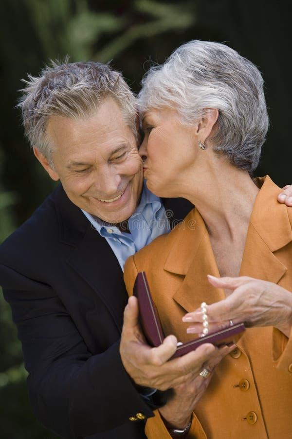 Frau, die Ehemann auf Backe küsst lizenzfreie stockfotos