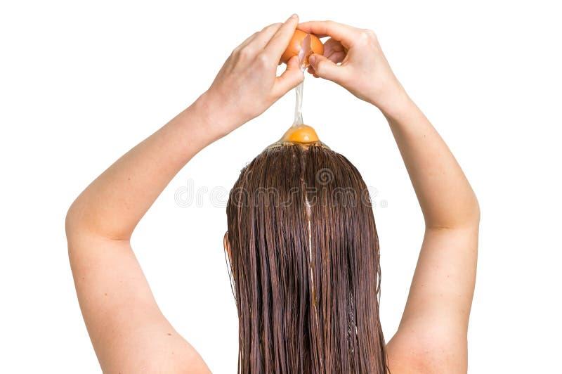Frau, die Eiconditioner auf ihrem Haar anwendet stockbild