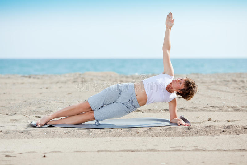 Frau, die Eignungübung auf Strand tut stockbilder