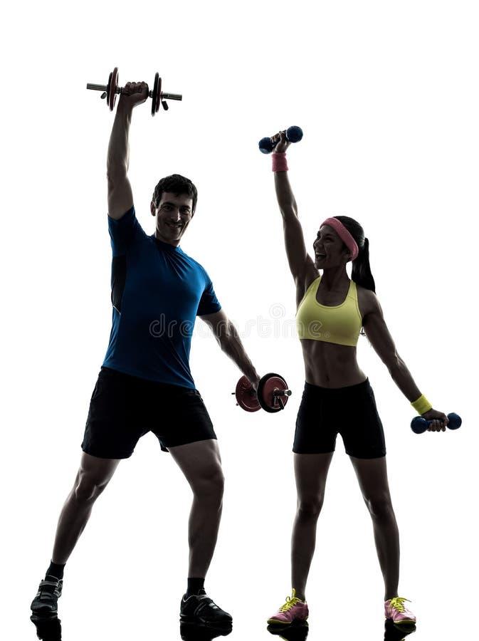 Frau, die Eignungstraining mit Manntrainerschattenbild ausübt stockfotos