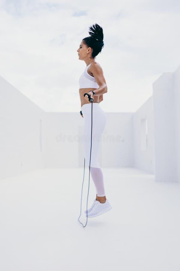 Frau, die Eignungstraining unter Verwendung eines Springseils tut lizenzfreie stockfotografie