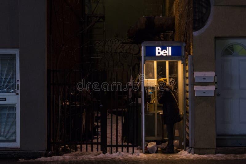 Frau, die ein Bell Canada-Münztelefon in Montreal am Abend unter starken Schneefällen verwendet lizenzfreies stockfoto
