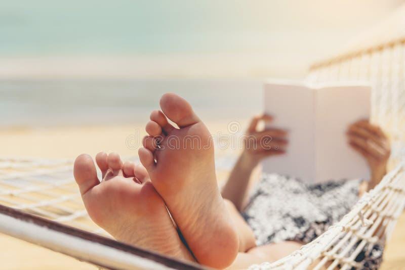 Frau, die ein Buch auf H?ngemattenstrand in den FreizeitSommerferien liest lizenzfreies stockbild