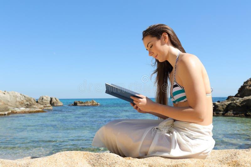Frau, die ein Buch auf Sommerferien auf dem Strand liest stockbilder