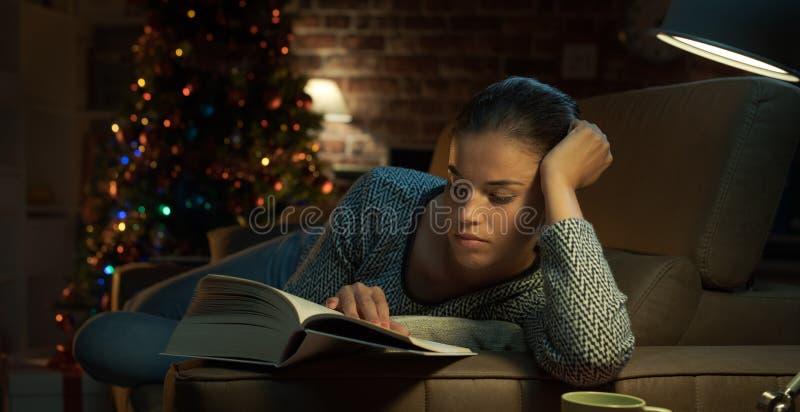 Frau, die ein Buch auf Weihnachtsabend liest stockfotografie