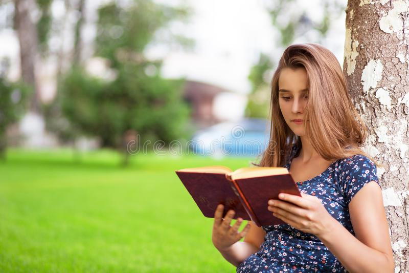 Frau, die ein Buch beim Sitzen lesend im Campus studiert lizenzfreies stockbild