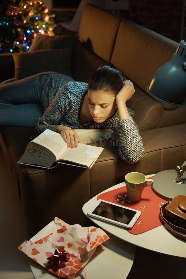 Frau, die ein Buch liest, das sie als Geschenk empfing lizenzfreie stockfotos