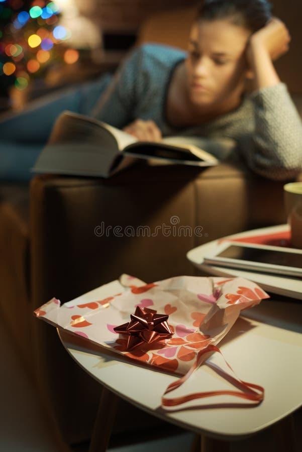 Frau, die ein Buch liest, das sie als Geschenk empfing stockbilder