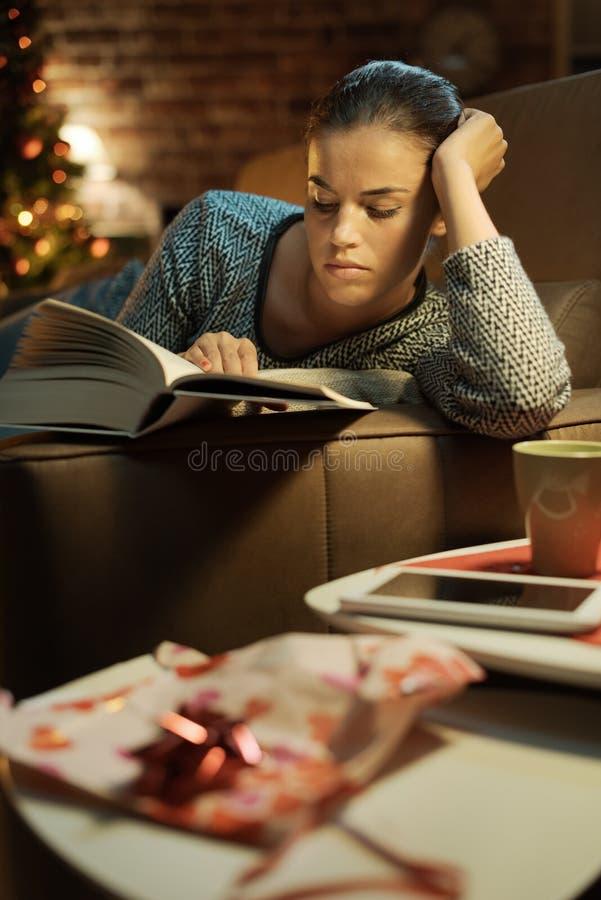 Frau, die ein Buch liest, das sie als Geschenk empfing lizenzfreies stockfoto