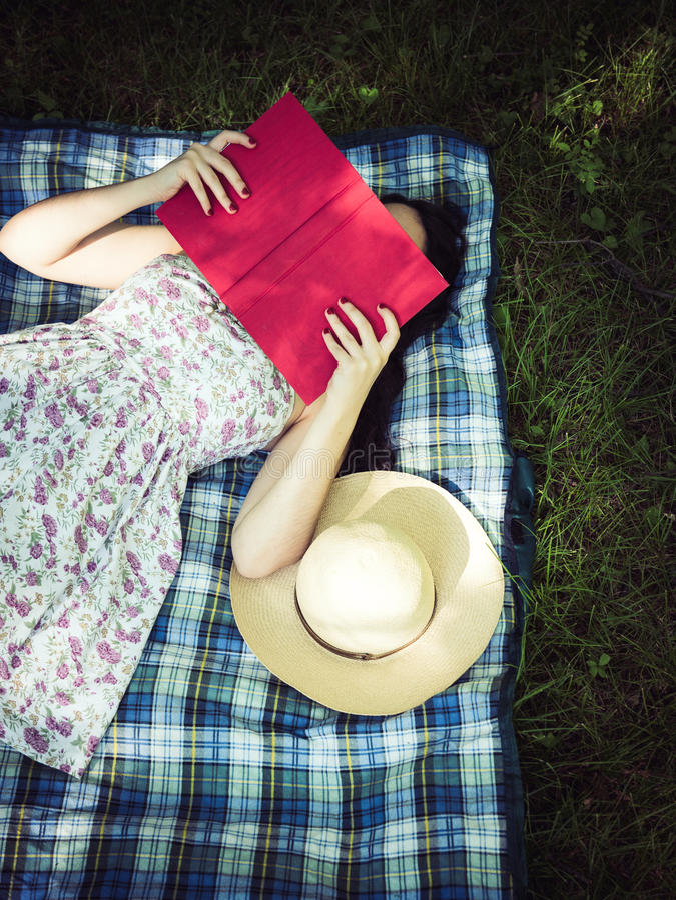 Frau, die ein Buch liest und draußen Gesicht bedeckt lizenzfreie stockfotografie