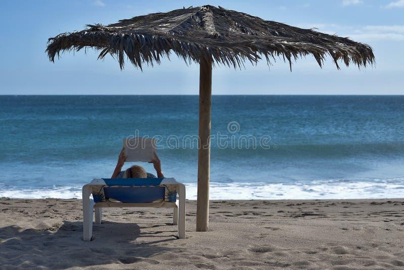 Frau, die ein Buch am Strand liest lizenzfreie stockfotos