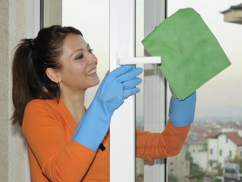 Frau, die ein Fenster säubert stockbild
