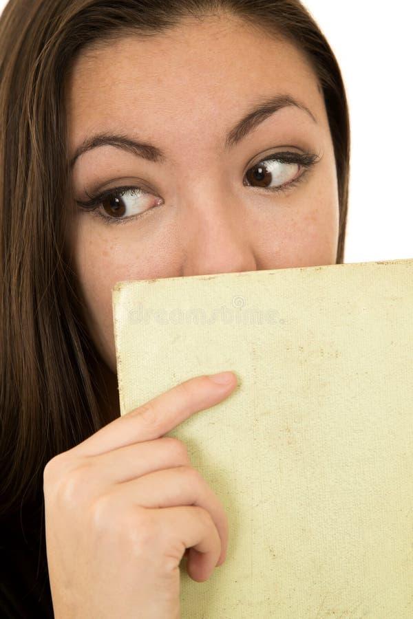 Frau, die ein flüchtig blickt Buch zu ihrem Gesicht seitwärts, halten lizenzfreie stockbilder