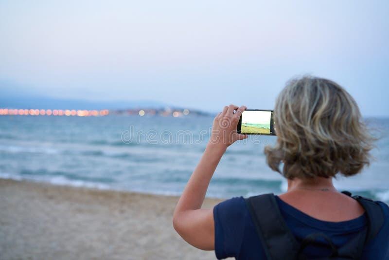 Frau, die ein Foto von einem Meer am intelligenten Telefon auf Sonnenuntergang macht stockfotografie