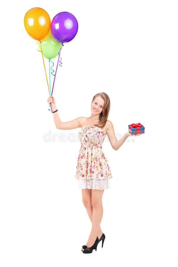 Frau, die ein Geschenk und ein Bündel Ballone hält stockbild