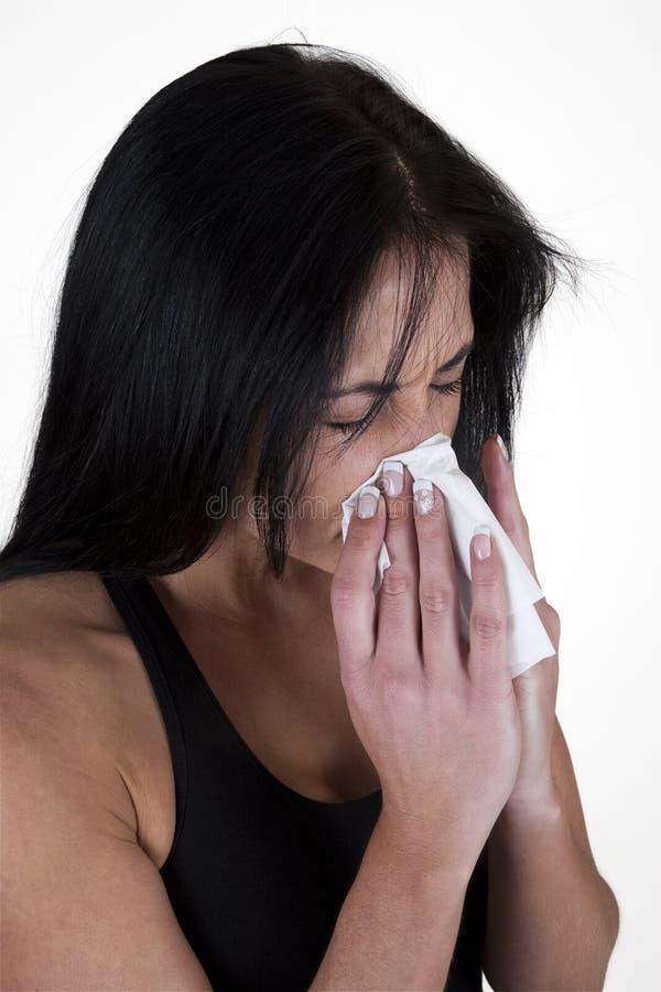 Frau, die in ein Gewebe niest stockfotos