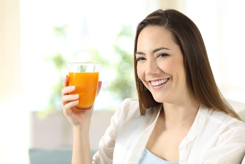 Frau, die ein Glas Orangensaft Sie betrachtend hält lizenzfreie stockfotografie