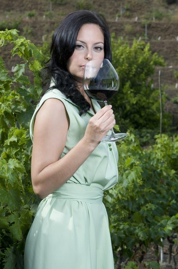 Frau, die ein Glas Rotwein schmeckt lizenzfreie stockfotos