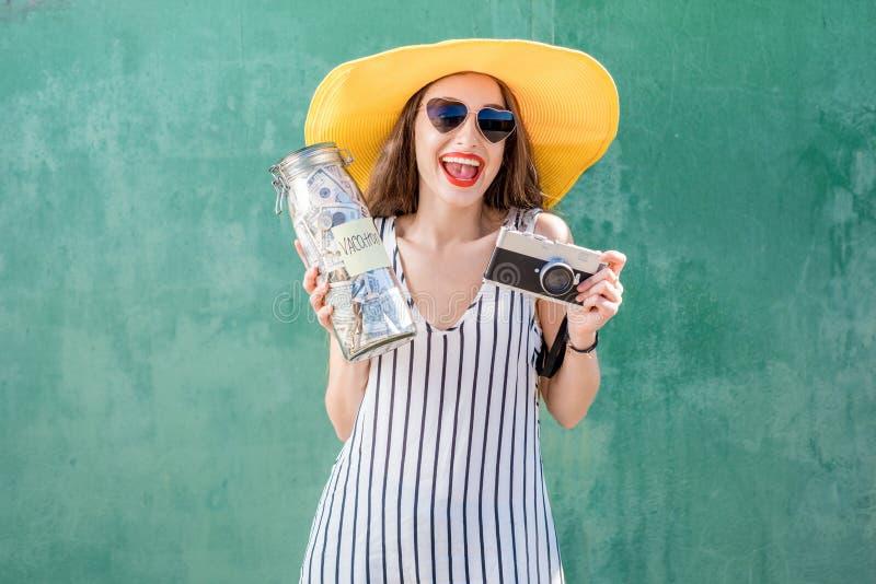 Frau, die ein Glas voll vom Geld für Sommerferien hält lizenzfreie stockfotografie