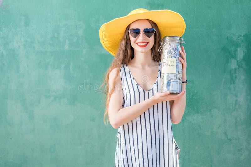 Frau, die ein Glas voll vom Geld für Sommerferien hält stockbild