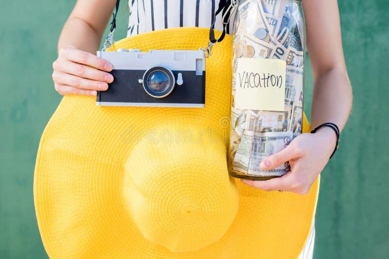 Frau, die ein Glas voll vom Geld für Sommerferien hält lizenzfreie stockbilder