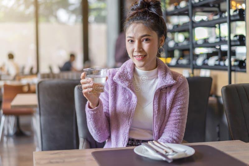 Frau, die ein Glas Wasser im Restaurant trinkt lizenzfreies stockfoto