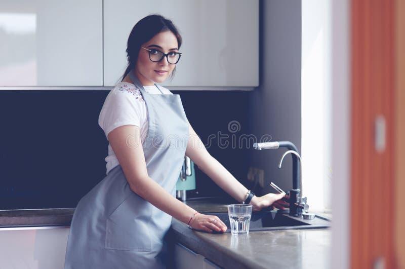 Frau, die ein Glas Wasser von einem Edelstahl oder ein Chromhahn oder -hahn füllt lizenzfreie stockfotos
