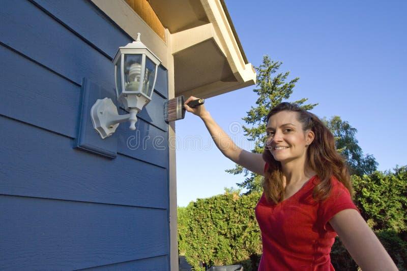 Frau, die ein Haus - horizontal malt lizenzfreies stockfoto