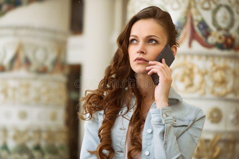 Frau, die ein intelligentes Telefon in der Straße verwendet stockfotografie