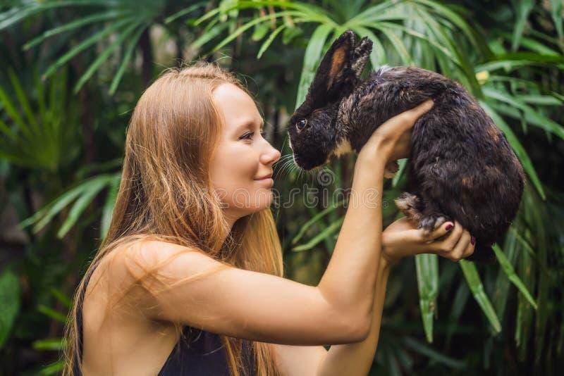 Frau, die ein Kaninchen anh?lt Kosmetik prüfen auf Kaninchentier Grausamkeit frei und Endtiermissbrauchskonzept lizenzfreie stockbilder
