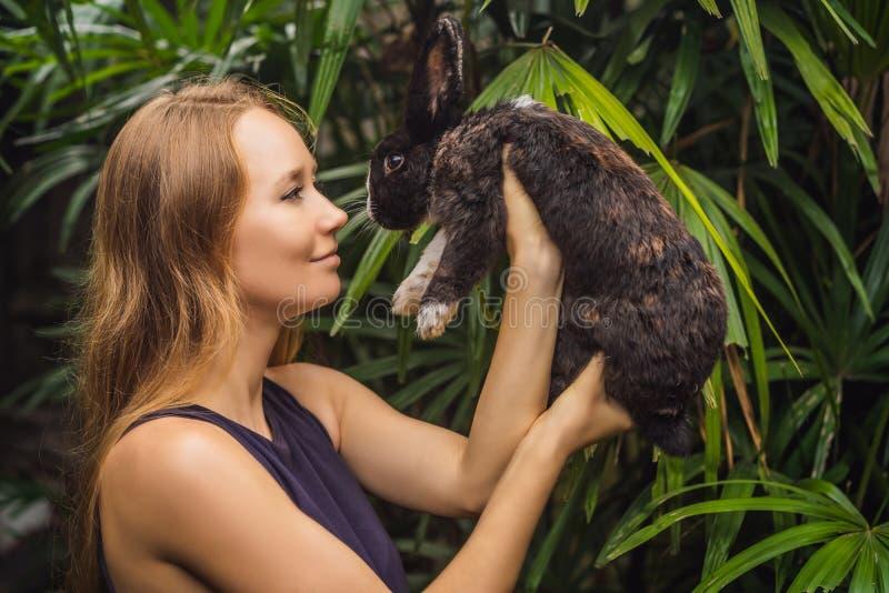 Frau, die ein Kaninchen anh?lt Kosmetik prüfen auf Kaninchentier Grausamkeit frei und Endtiermissbrauchskonzept lizenzfreies stockbild
