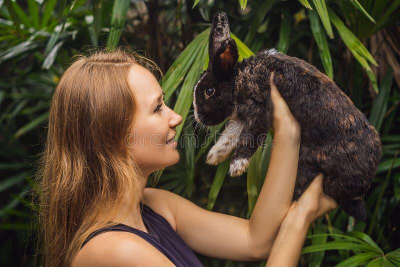 Frau, die ein Kaninchen anh?lt Kosmetik prüfen auf Kaninchentier Grausamkeit frei und Endtiermissbrauchskonzept stockfotografie