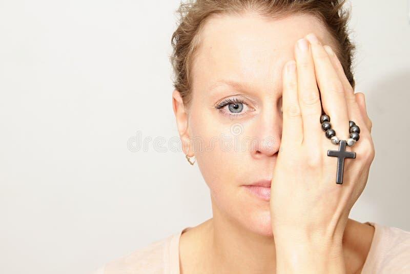 Frau, die ein Kreuz in ihren Händen hält stockfoto