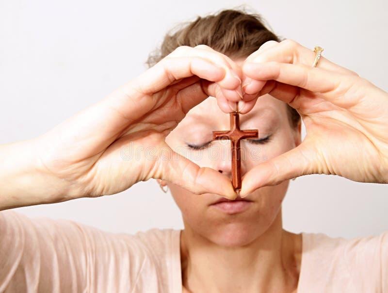 Frau, die ein Kreuz in ihren Händen hält lizenzfreies stockbild