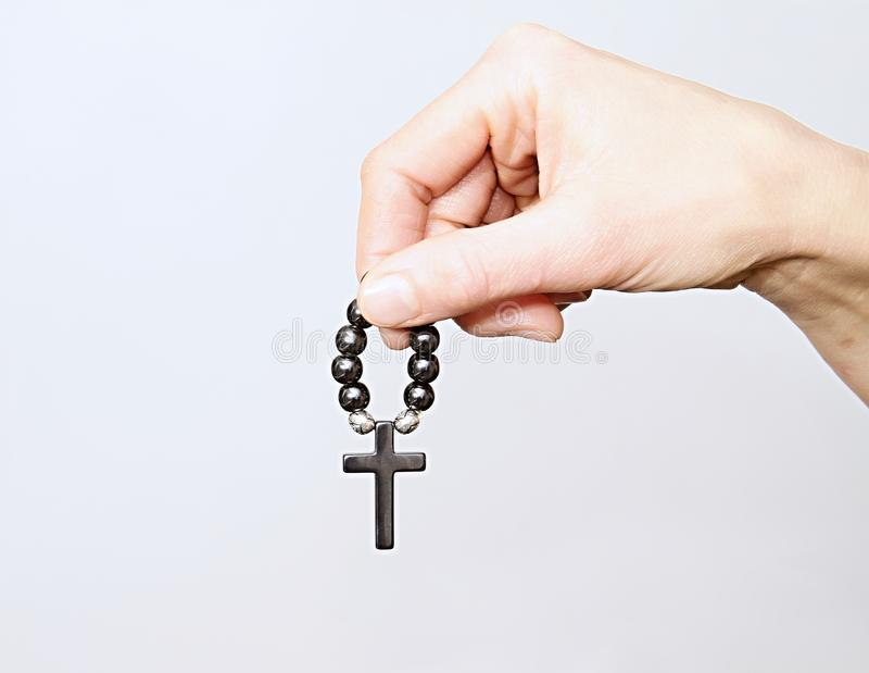 Frau, die ein Kreuz mit Rosenkranzperlen hält lizenzfreie stockfotografie