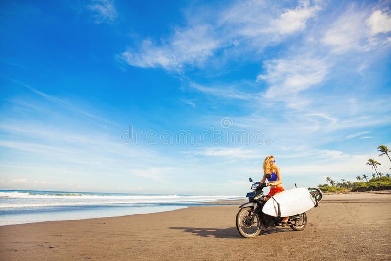 Frau, die ein Motorrad mit dem Surfbrett reitet stockfotografie