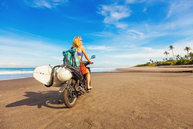Frau, die ein Motorrad mit dem Surfbrett reitet stockbild