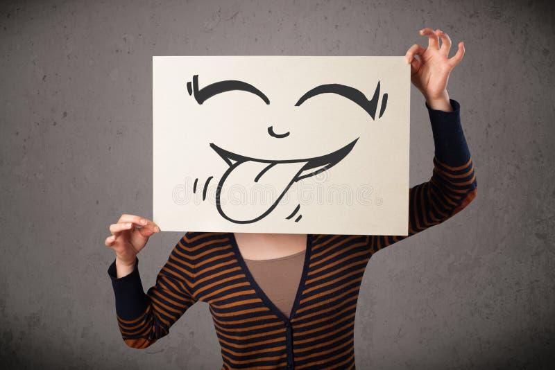 Frau, die ein Papier mit nettem smileygesicht auf ihm vor ihm hält lizenzfreie stockbilder