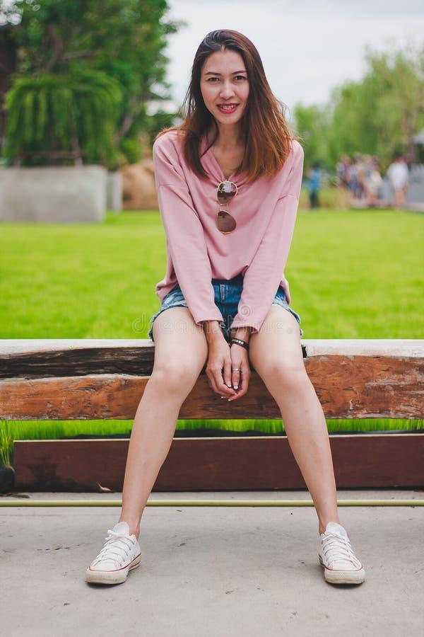 Frau, die ein rosa Hemd sitzt auf einem langen Stock trägt lizenzfreies stockbild