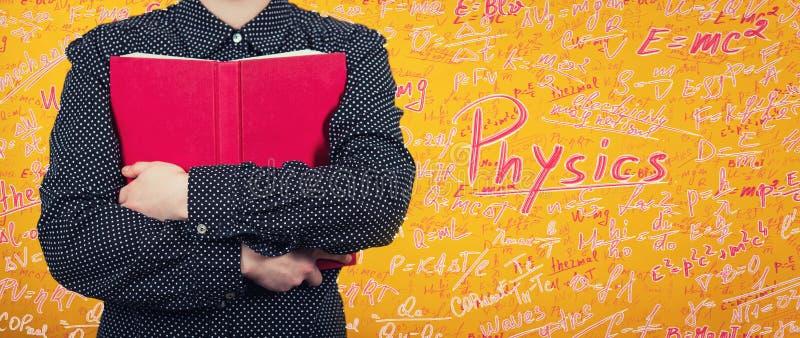 Frau, die ein rotes Buch zum Kasten Ausbildungskonzept als Student umarmt ein Lehrbuch, liebendes Wissen lokalisiert über gelber  lizenzfreie stockfotografie