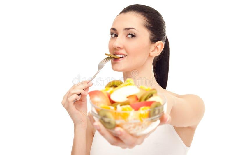 Frau, die ein Stück der Kiwi isst lizenzfreies stockfoto
