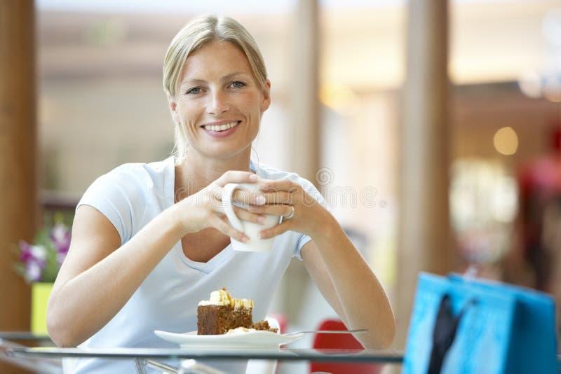 Frau, die ein Stück des Kuchens am Mall isst lizenzfreies stockbild