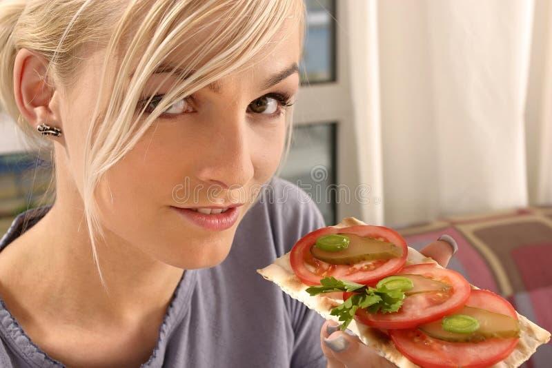 Frau, die ein Tomatesandwich isst stockfotografie