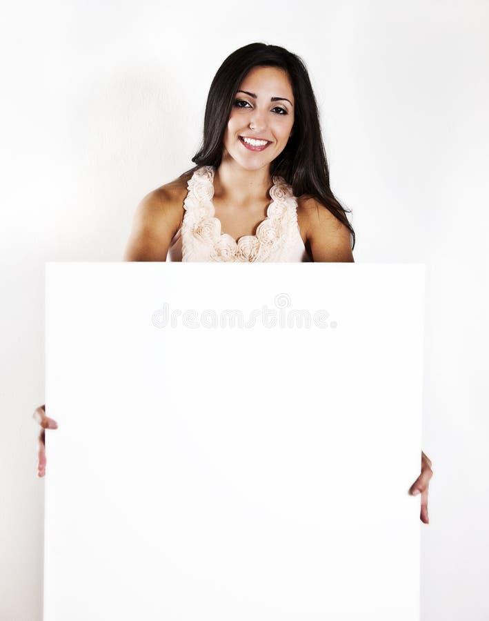 Frau, die ein unbelegtes weißes Zeichen anhält lizenzfreie stockbilder