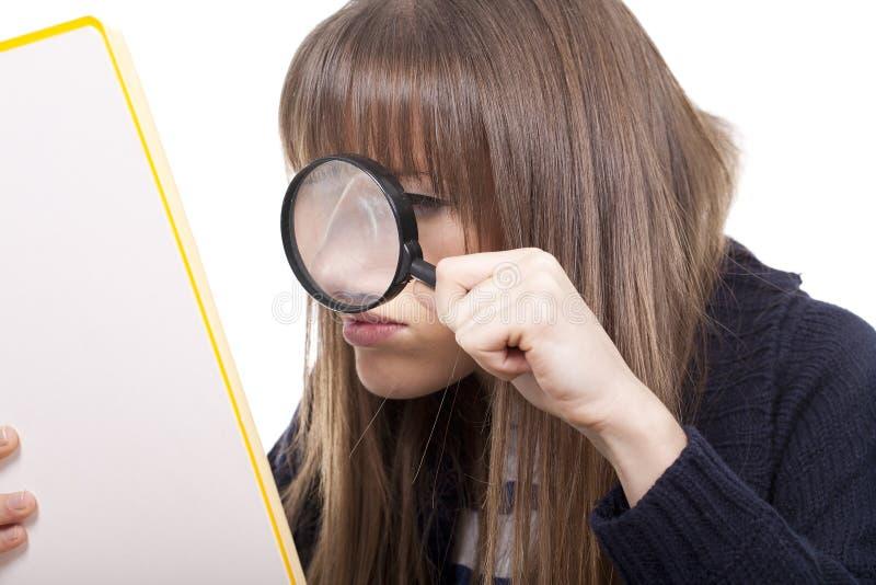 Frau, die ein Vergrößerungsglas anhält stockbild
