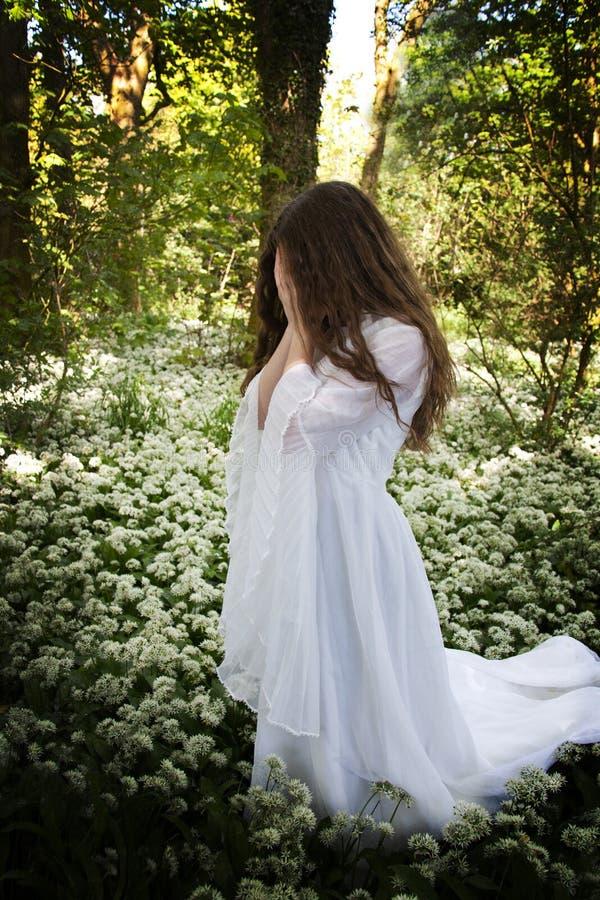 Frau, die ein weißes Kleid steht in einem Wald trägt lizenzfreie stockfotografie