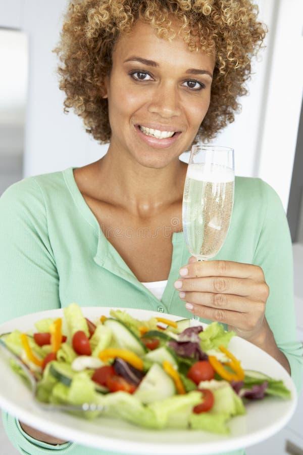 Frau, die ein Wein-Glas und einen frischen Salat anhält lizenzfreies stockfoto