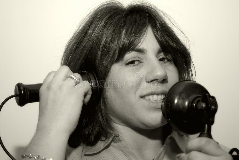 Frau, die ein Weinlese-Telefon verwendet lizenzfreies stockfoto