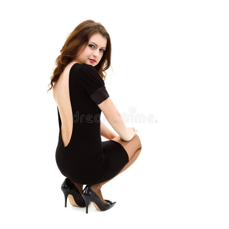 Frau, die ein wenig schwarzes Kleidersitzen trägt stockfoto